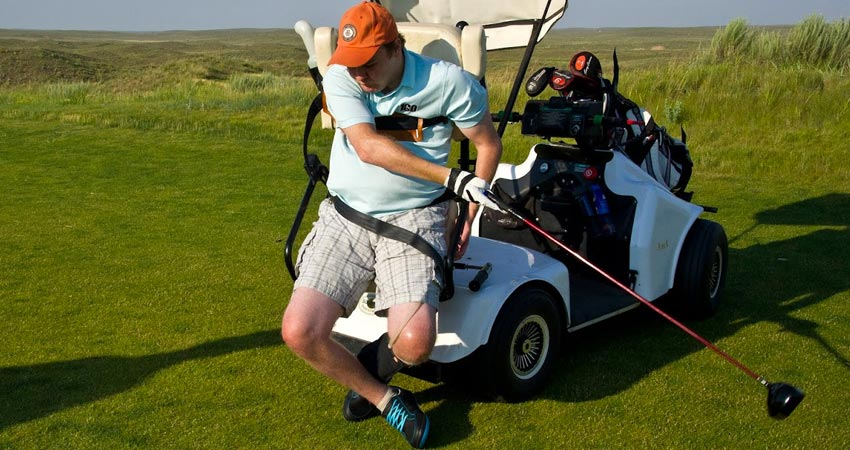 golfer sitting on the back of a golf cart