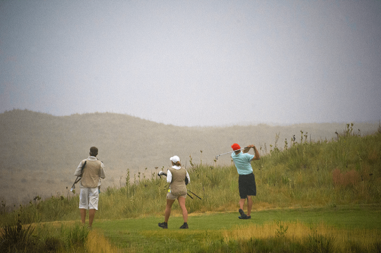 walking golfer with caddies